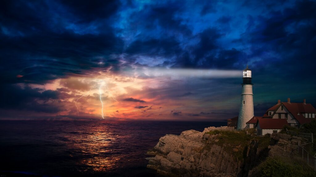 picture of a lighthouse brightening a dark, stormy sky